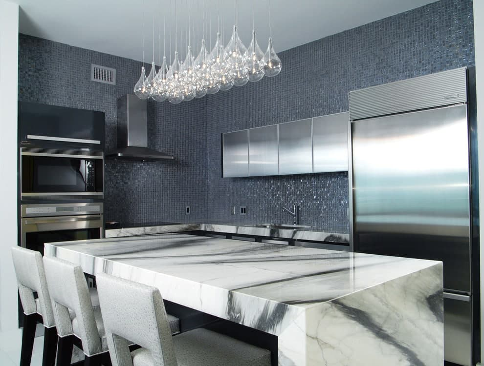 Glass drop pendants hang over the marble breakfast island that's paired with gray upholstered chairs. It is accompanied by stainless steel appliances and cabinets against the sparkling mosaic backsplash tiles.