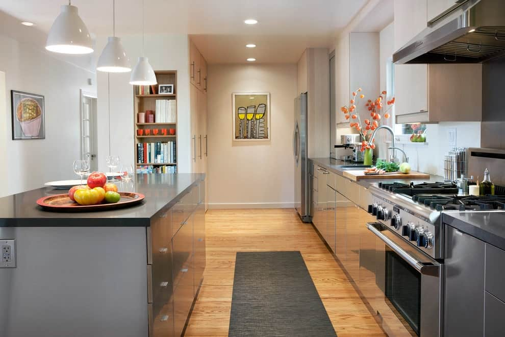 Silver cabinets and a matching kitchen island flank a gray runner that lays on the natural hardwood flooring. It is illuminated by recessed ceiling lights and white dome pendants.