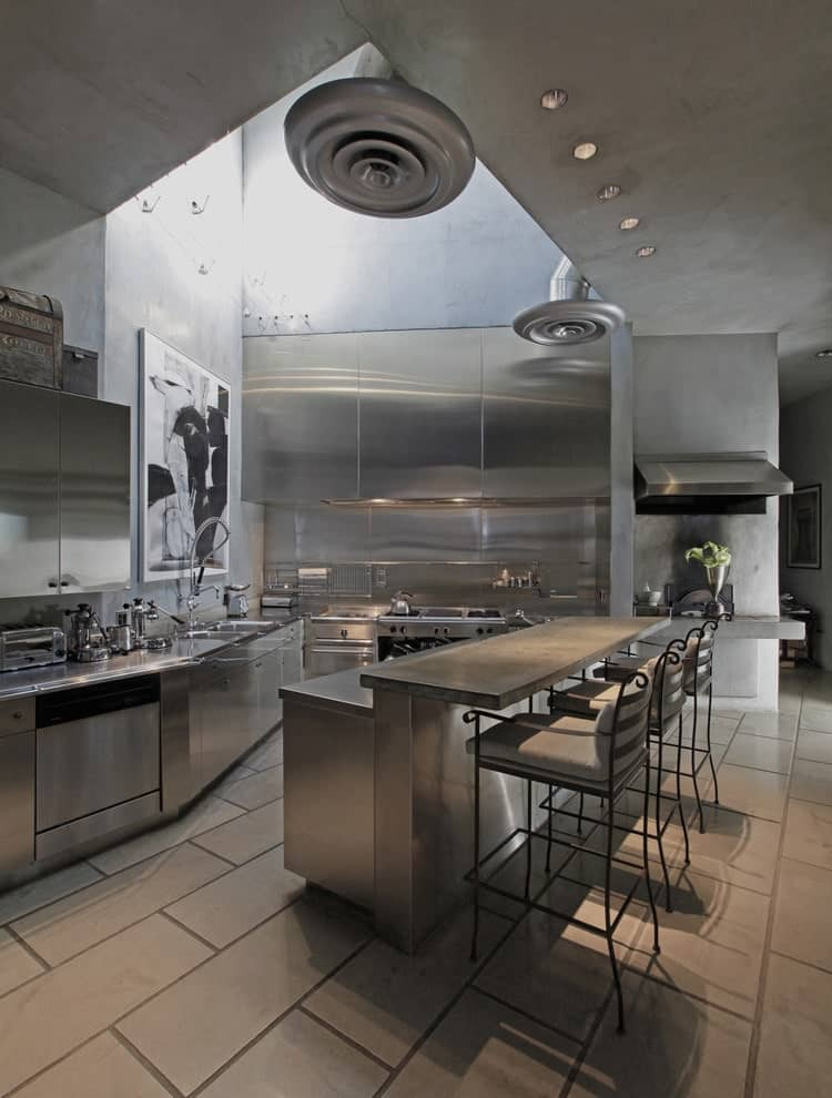 This kitchen is decorated with a large artwork mounted on the concrete wall. It has stainless steel appliances and a two-tier island bar with metal counter chairs over brick flooring.