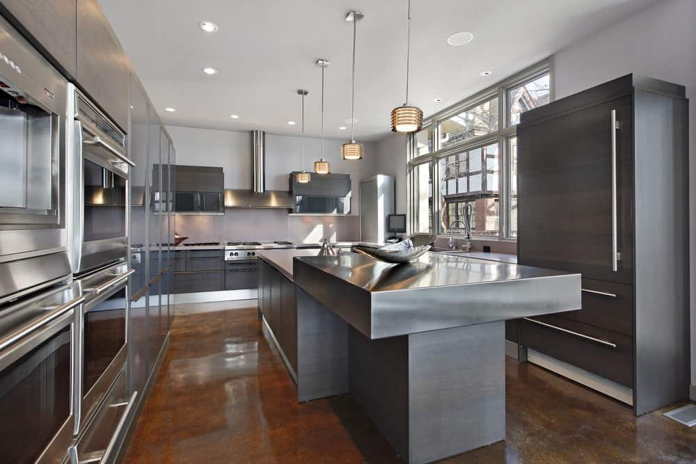 Silver kitchen with inset appliances and cabinetry complementing with the raised island bar over stained concrete flooring. It is illuminated by industrial pendants and recessed ceiling lights.