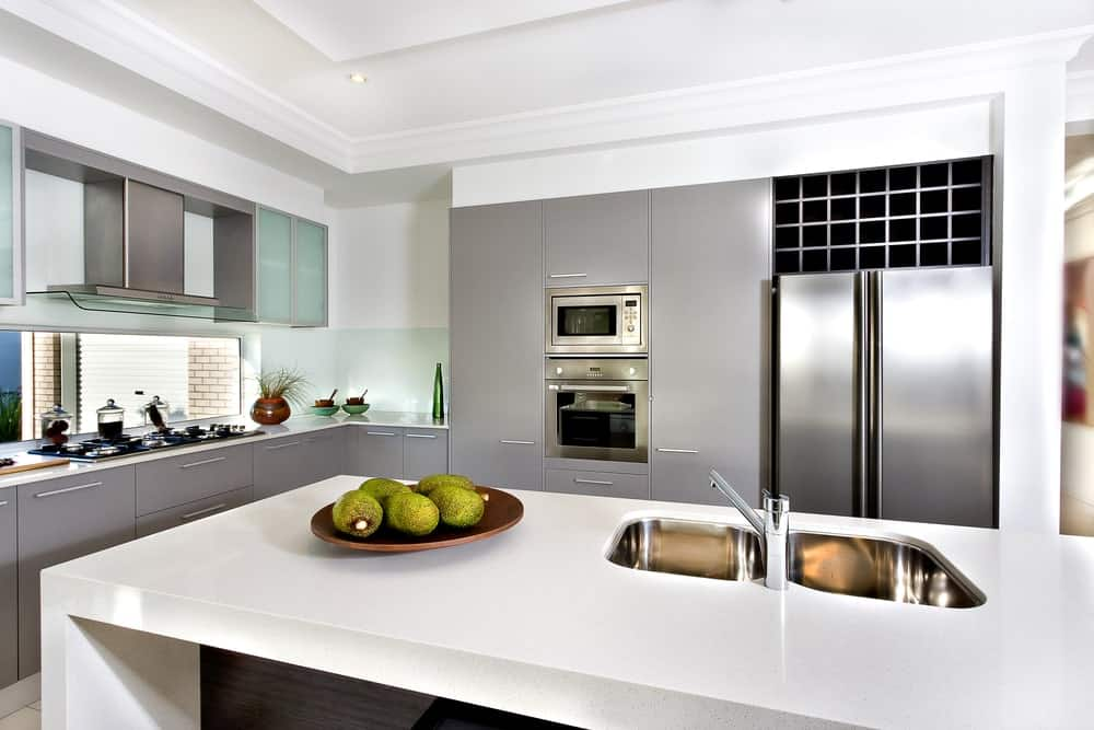 Stainless steel fridge stands under a cubby wine rack facing the white granite top island that's fitted with a dual sink and chrome faucet. It is accompanied by inset appliances and gray cabinetry.