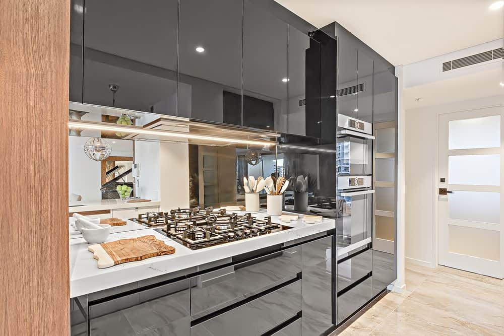 A white frosted glass door opens to this deluxe kitchen with mirrored backsplash and high glass cabinetry contrasted by a white marble countertop that's fitted with a built-in cooktop.