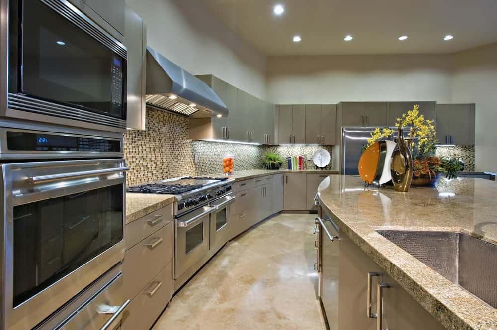 The luxury kitchen features stainless steel appliances and gray cabinetry accented with stunning mosaic backsplash tiles. There's an island bar on the side that's fitted with built-in storage and an undermount sink.