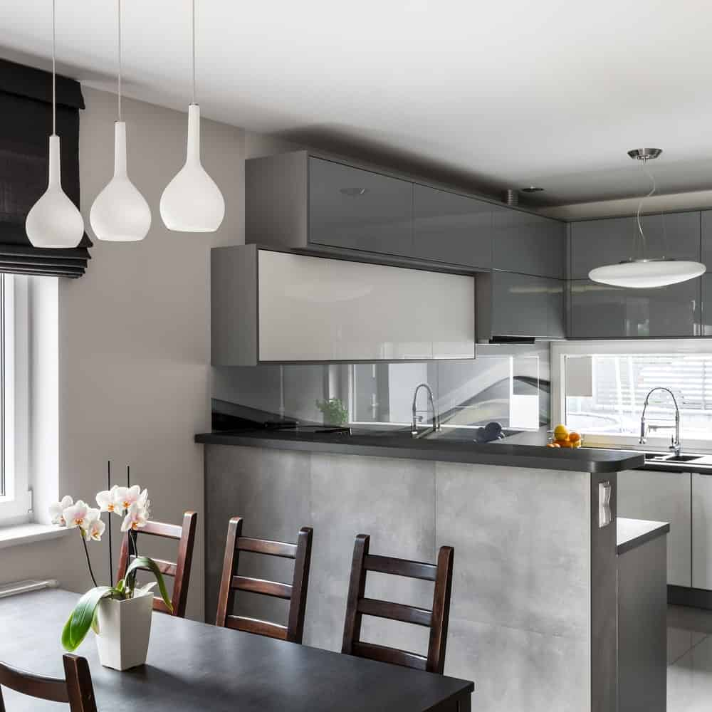 An eat-in kitchen with high gloss cabinetry and a concrete two-tier peninsula topped with gray countertops. It includes a dark wood dining set illuminated by white pendant lights.