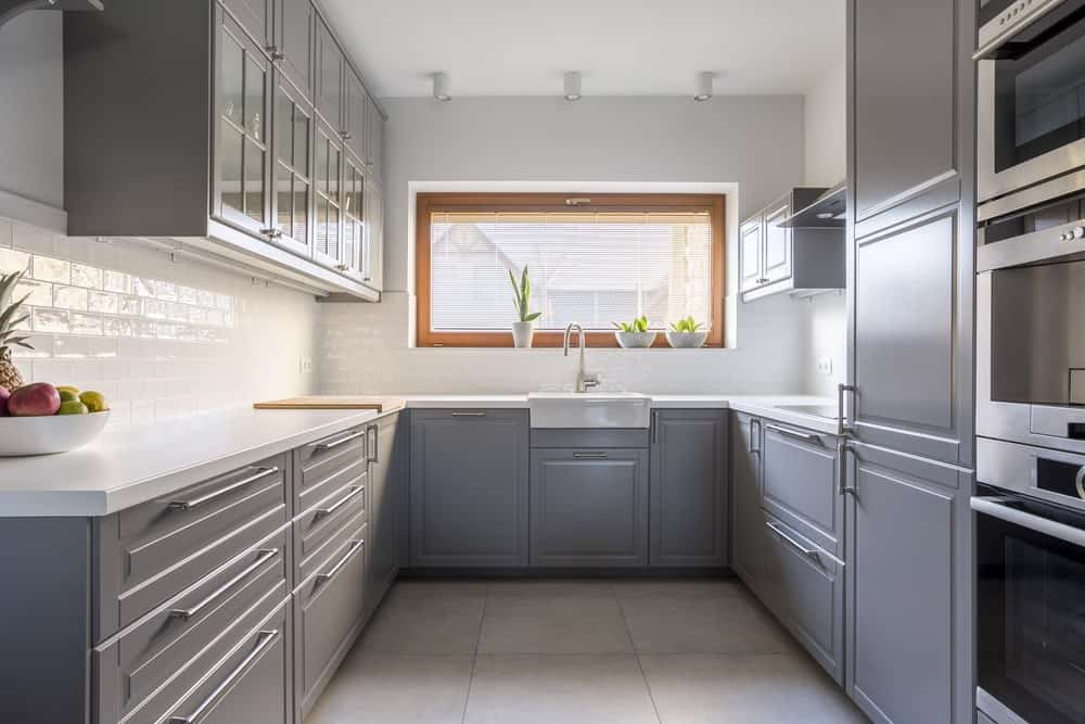 Fresh kitchen showcases stainless steel appliances and gray cabinetry against the white subway tile backsplash. It includes white track lights and a farmhouse sink paired with a gooseneck faucet.