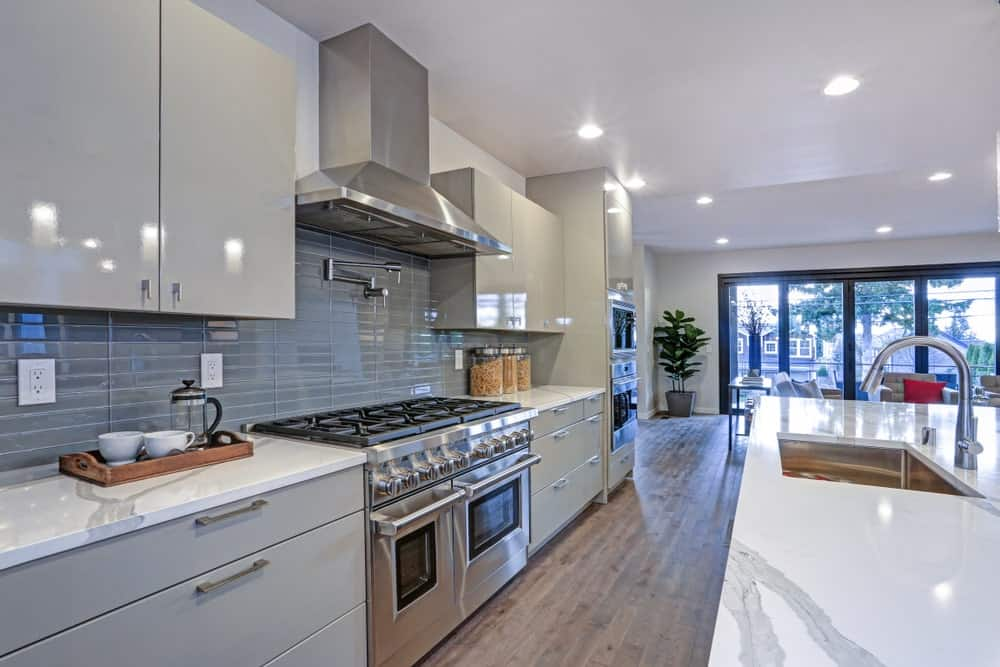 An open kitchen with a galley layout offering marble top island and stainless steel range under a vent hood that's fixed above the gray backsplash. It has natural hardwood flooring and regular white ceiling mounted with recessed lights.