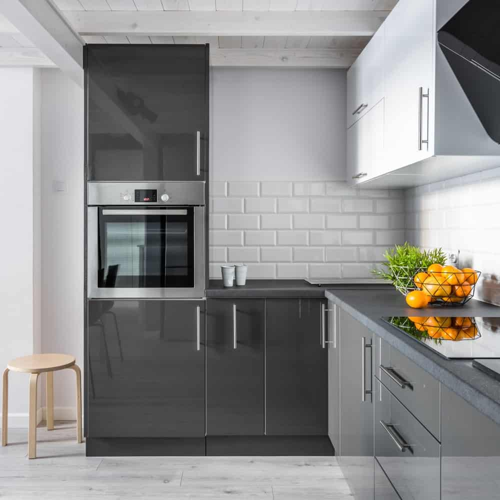 A wooden stool sits next to the high gloss cabinetry that's fitted with a stainless steel oven. This kitchen boasts concrete countertops that are contrasted by white subway tile backsplash.