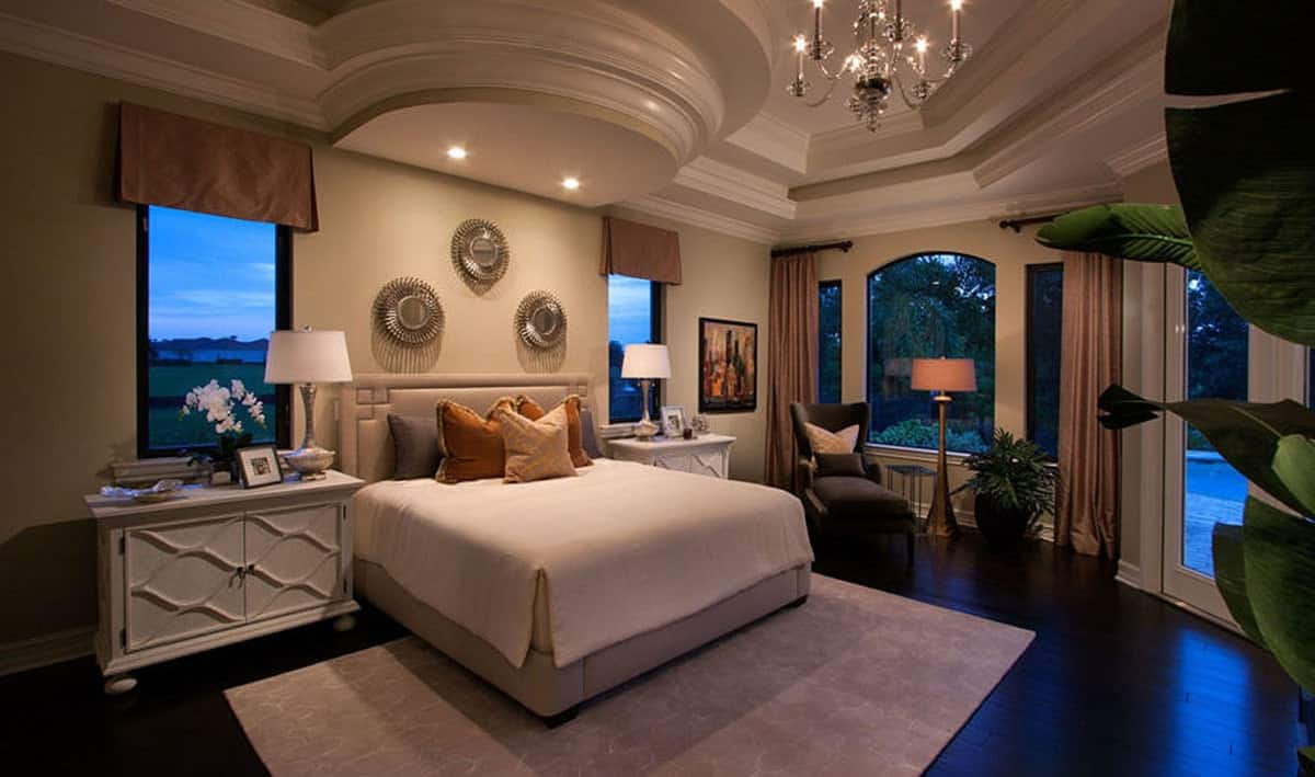 This is a very elegant primary bedroom with a lovely tray ceiling with a chandelier and a an alcove over the bed with recessed lights to warm up the beige bed and its bedside drawers.