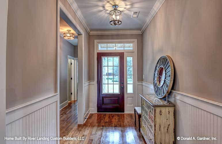 Foyer with a wooden entry door, semi-flush light, and a rustic console table topped with a round clock. These are then complemented by natural lights and wainscoting.