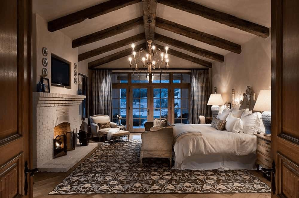 A candle chandelier illuminates this primary bedroom along with table lamps that sit on the wooden nightstands. It has a white skirted bed and a brick fireplace with a flat panel TV on top.