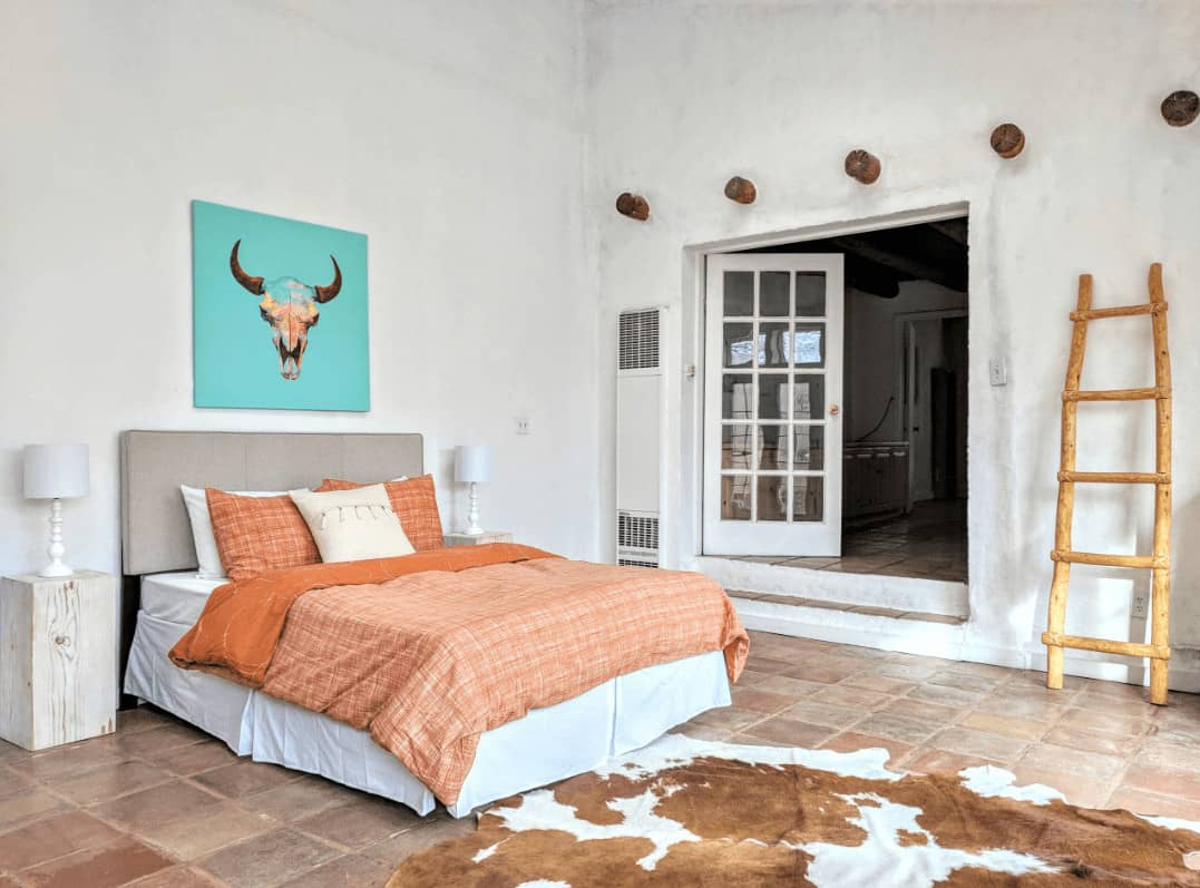 A bull head artwork adds a nice accent in this white bedroom with a gray skirted bed and cowhide rug that lays on the terracotta flooring.