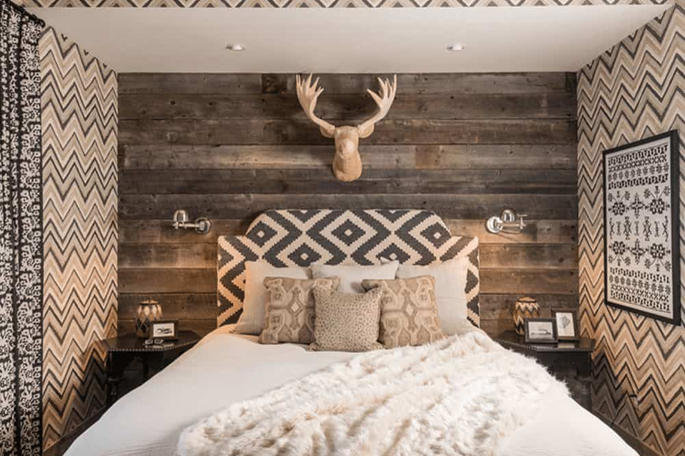 Clad in chevron wallpaper and rustic wood plank, this primary bedroom boasts a deer head decor and comfy bed flanked by hexagonal nightstands and chrome sconces.