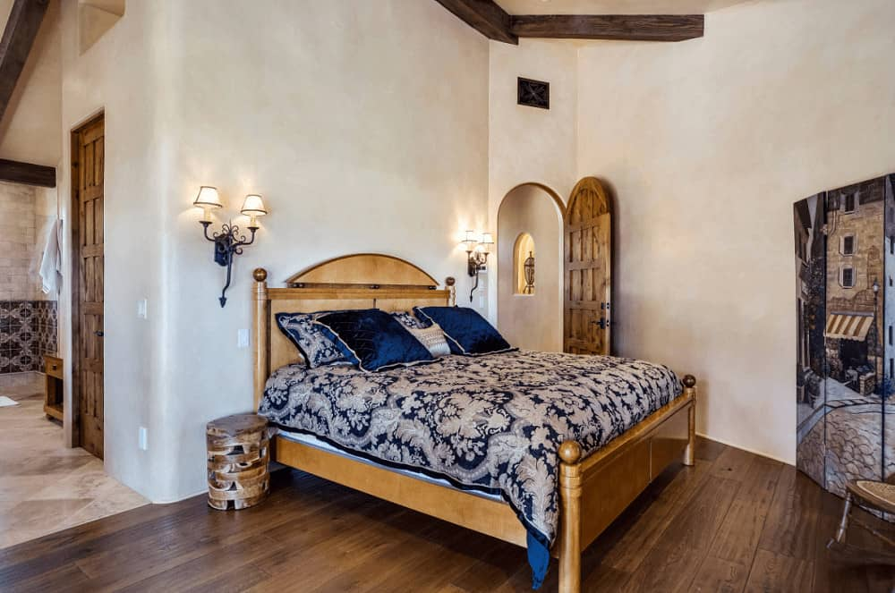 An arched carved wood door opens to this cozy bedroom with wrought iron sconces and a wooden bed dressed in blue floral bedding.