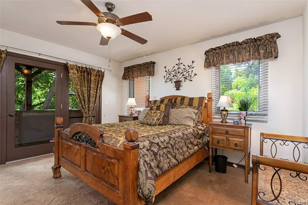 The glass doors and windows of this Southwestern-style bedroom has floral curtains that match the patterns of the brown bed sheet and pillows. This works well with the wooden frame of the sleigh bed paired with wooden bedside drawers as well as a daybed on the side.