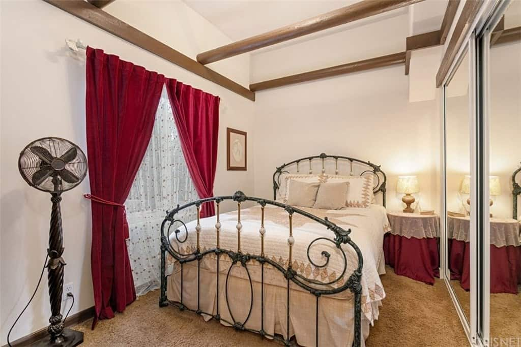 The impressive beige ceiling that blends with the beige walls are adorned with a single exposed wooden beam that blends with the molding. The beige walls also match with the bed sheet that is contrasted by the wrought iron frame of the bed.