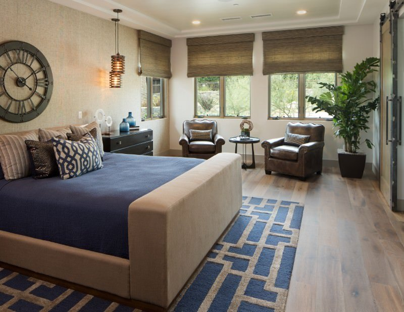 The beautiful blue sheet of the light gray sleigh bed matches with the blue patterned area rug underneath that tops the hardwood flooring. This is matched with the brown leather cushioned armchairs at the sitting area on the side by the windows.