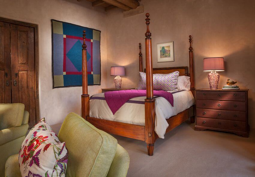 This Southwestern-style bedroom has a wooden pencil poster bed with light colors on its bed sheets that match with the bold colors of the tapestry hanging on the white wall at the side adjacent to the table lamp of the bedside drawer that matches the hue of the bed frame.