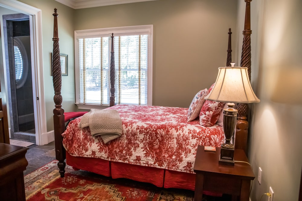 The red floral patterned bed sheet of the four-poster bed matches with the red patterned area rug underneath. This mostly covers the earthy flooring of the Southwestern-style bedroom complemented by the light gray walls and white window with blinds.