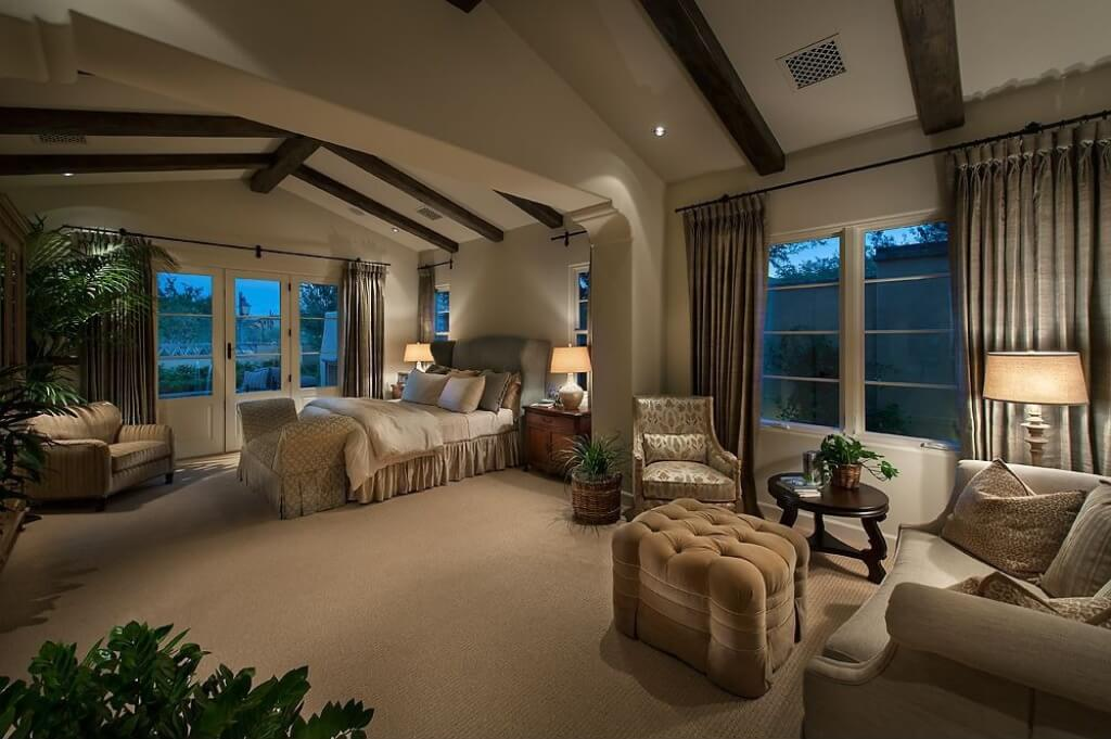 This homey and elegant Southwestern-style primary bedroom has a spacious beige carpeted flooring that matches with the beige traditional bed, beige walls and beige cathedral ceiling that is contrasted by its dark wooden exposed beams.