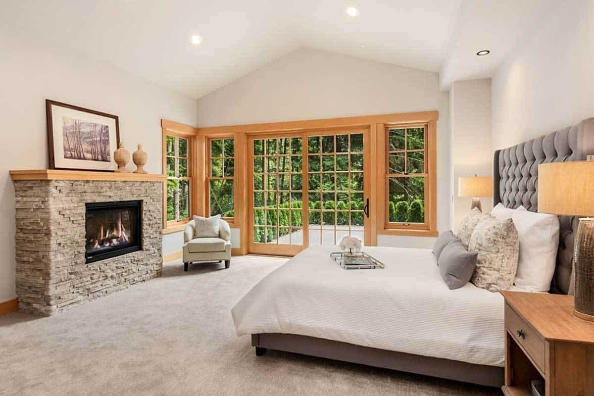 This spacious bedroom has a light beige cathedral ceiling that blends with the walls adorned with a stone fireplace across from the gray bed that has a cushioned headboard.