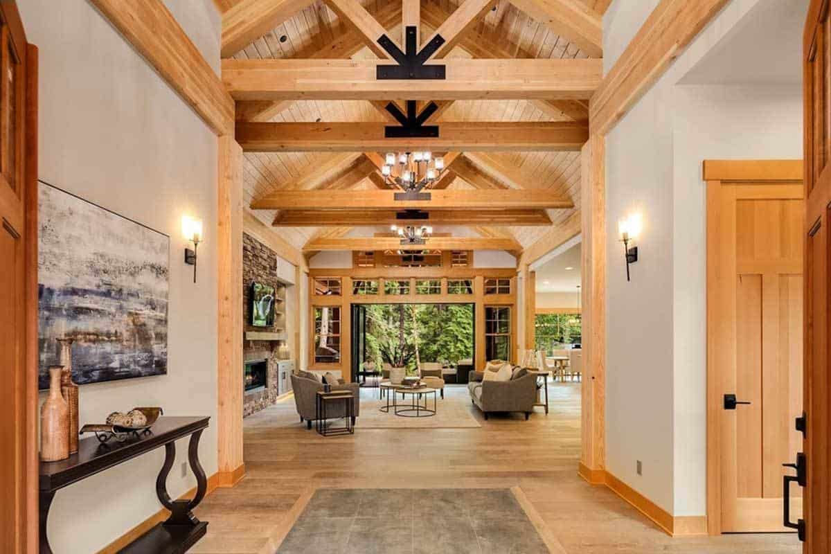 This foyer has a homey quality to its wooden ceiling with exposed beams matching the moldings of the white walls that have sconces. There is also a dark console table on the side topped with a painting.
