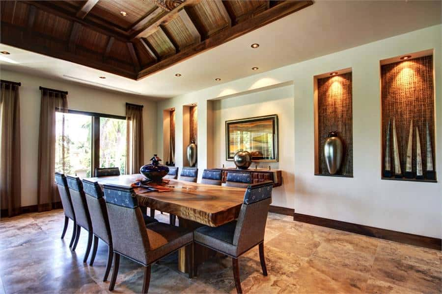 This dining room has a rustic and homey wooden dining table surrounded by dark brown chairs. These chairs match the tone of the wooden tray ceiling that has carving and beams.