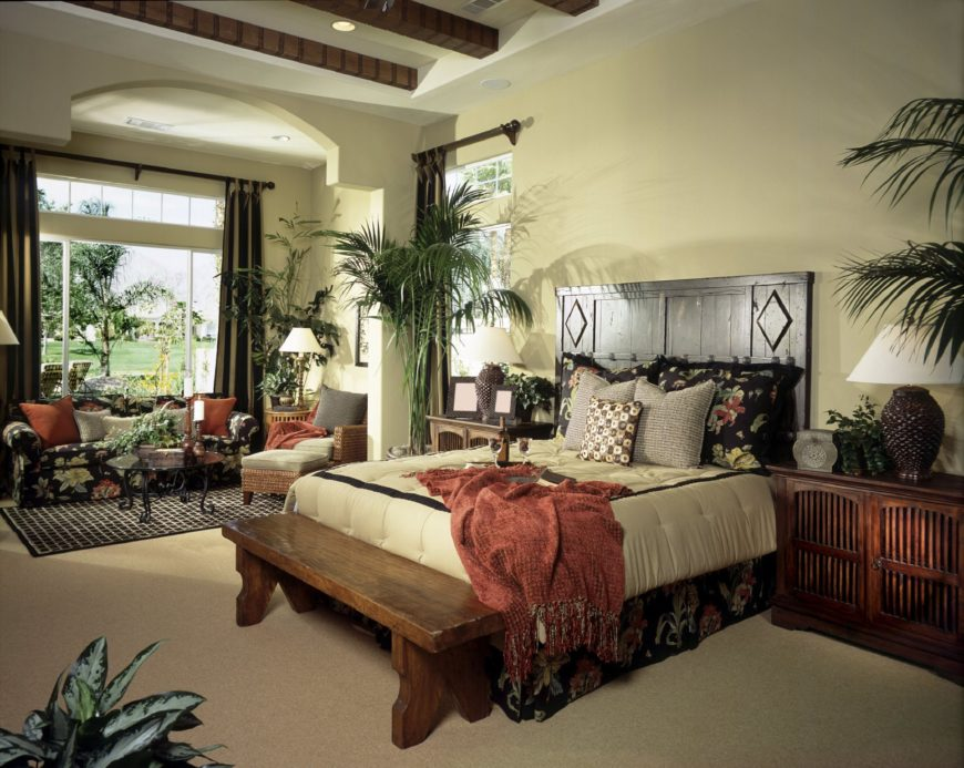 Fresh bedroom offers a beadboard bed with a wooden bench on its end along with a black floral sofa accompanied by a round glass top coffee table and gray lounge chair.