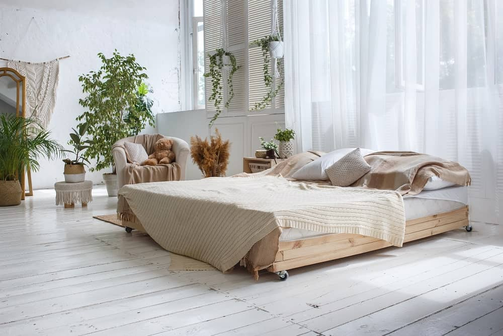 Light and airy bedroom offers a wooden bed with wheels accompanied by a matching nightstand and white round back chair. It has distressed wide plank flooring and glazed windows covered in flowy sheer curtains.