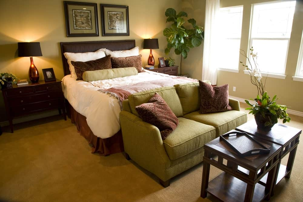 Tropical bedroom with a brown skirted bed and green couch paired with wooden coffee tables. It has carpet flooring and glazed windows allowing natural light in.