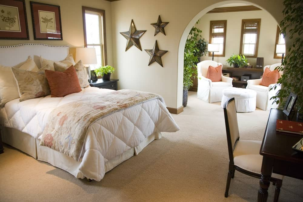 Charming bedroom with carpet flooring and an open archway leading to the seating area. It has star wall arts and white skirted bed that faces the dark wood desk paired with a beige cushioned chair.