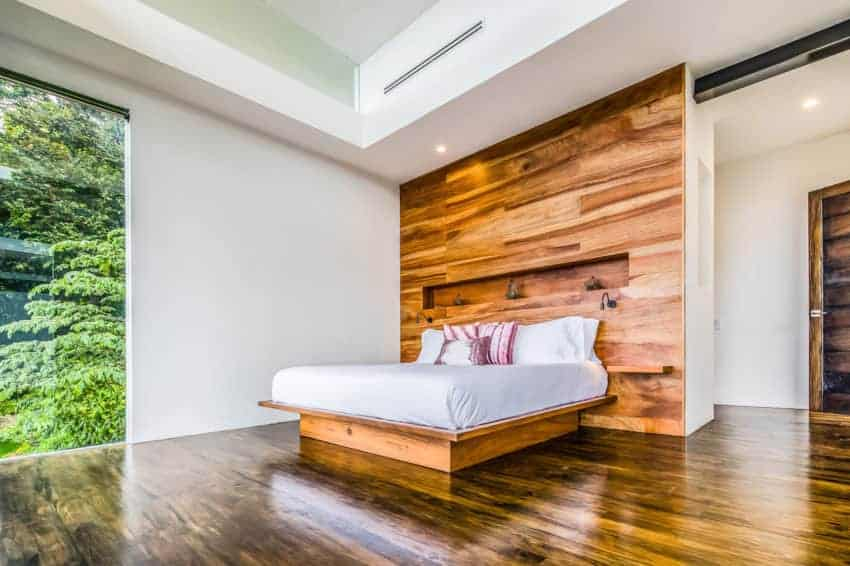 The wooden platform bed that carries the white cushion and its pillows blend with the large wooden wall that serves as a large headboard. This has a redwood hue that contrasts with the white walls, white tray ceiling and the glass windows.