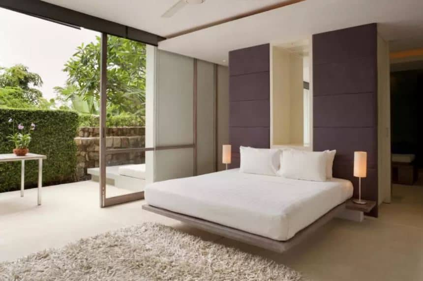 The modern floating platform bed has a white cushion that stands out against the dark gray headboard. The white bed is further brightened by the natural lights coming in from the large sliding glass doors with tropical trees and plants outside.