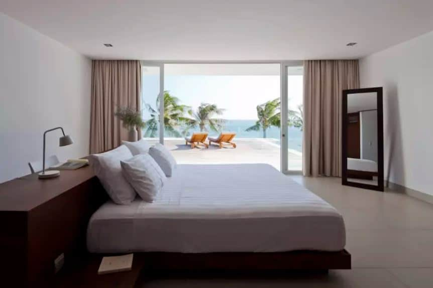 The highlight of this Tropical-style bedroom is the sublime scenery outside that has the tops of the coconut trees against the view of the ocean. This serves as a relaxing view for those are enjoying the simple white platform bed with a large wooden headboard.