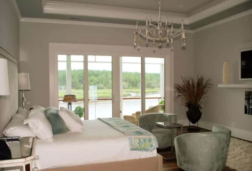 The simple light gray and white elements of the bed and the walls are complemented by the green velvet cushioned armchairs by the foot of the bed as well as the green pillow and bed scarf. These green elements are a mirroring of the beautiful green landscape outside the glass doors.