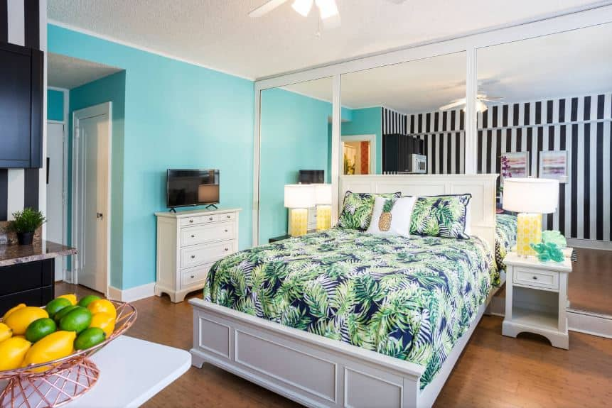 The highlight of this bedroom is the bed sheet and pillows of the bed that has a complex Tropical-style patterned design. This makes the bed stand out against the light gray sleigh bed and the hardwood flooring as well as the wall behind the bed that s dominated by large mirrors.