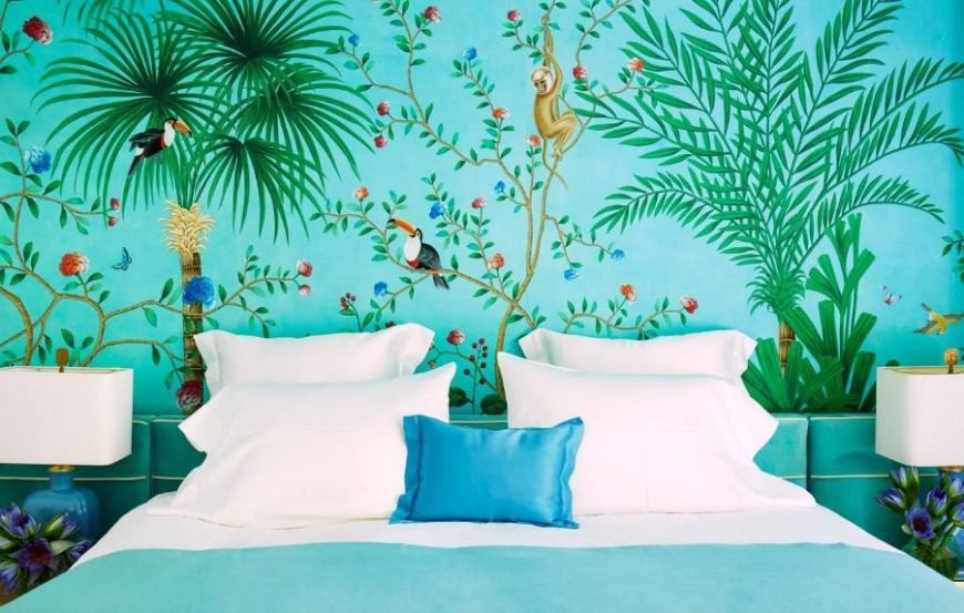 The bright white pillows and sheets of the traditional bed stands out against the green wallpaper of this Tropical-style bedroom that is filled with depictions of tropical plants and animals. This matches with the flowers on the bedside tables with the table lamps.