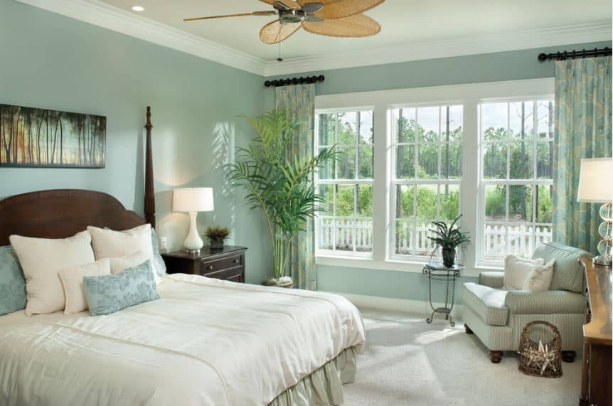 The cheerful green walls of this bedroom matches well with the green potted plant in the corner that complements the green landscape outside the tall windows as well as the colorful painting of trees mounted on the wall above the wooden headboard of the traditional bed.