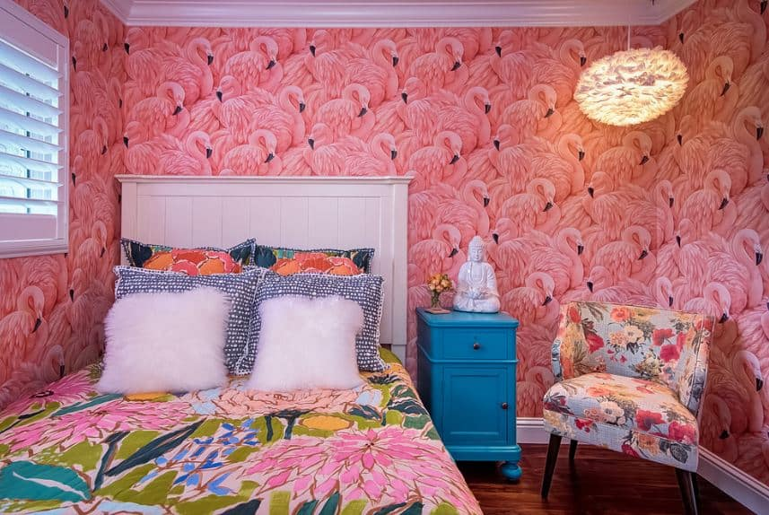 This is a fabulously chic Tropical-style bedroom that has walls dominated with a bright pink wallpaper with patterns of flamingos. This creates a complex background that matches with the colorful floral patterns on the bed sheet and cushioned chair beside the bed.