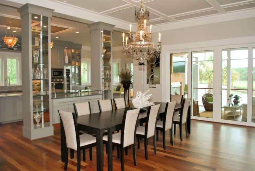 This elegant dining room that has a dark wooden table contrasted by its white-cushioned chairs is complemented by the hardwood flooring and the majestic chandelier. This setup makes the Tropical-style landscape outside more beautiful.