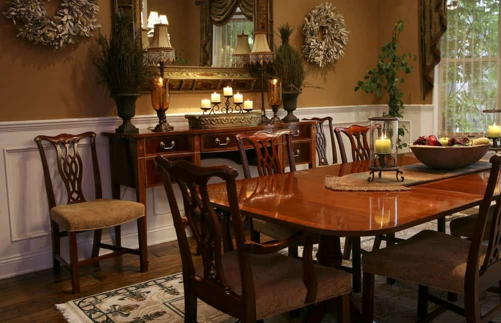 The elegant dark brown chairs, console table and large dining table are complemented by the hardwood flooring as well as the brown walls that are contrasted by the white wainscoting. These earthy tones are augmented by the potted plant on the corner as well as the decorations that came from plants.