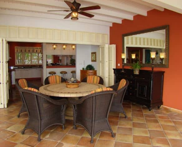 The earthy terracotta flooring tiles of this Tropical-style dining room complements the dark brown elements of the cabinet and the woven wicker dining chairs. It also complements the red wall that contrasts the white wooden ceiling with a dark brown ceiling fan in the middle.