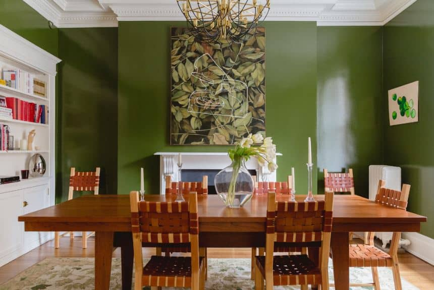 The green walls of this Tropical-style dining room make the white mantle of the fireplace stand out as well as the white wooden cabinet by the head of the wooden dining table. The white mantle is topped with a large painting of leaves.