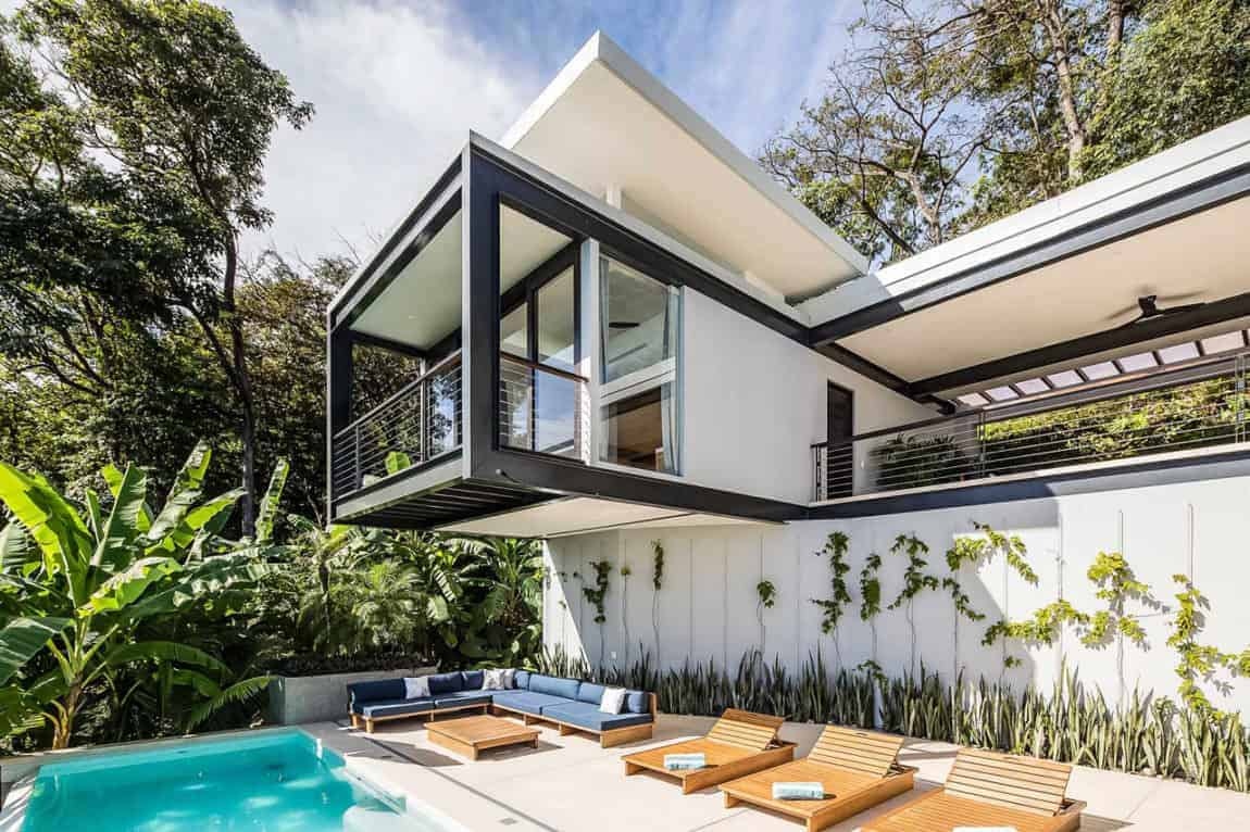 This is a beautiful pool side scene accented with a distinct Tropical-style landscaping. The swimming pool that stands out against the bleached concrete flooring that has an L-shaped wooden sofa along with three wooden lawn chairs. This has a background of white walls with creeping plants on it.
