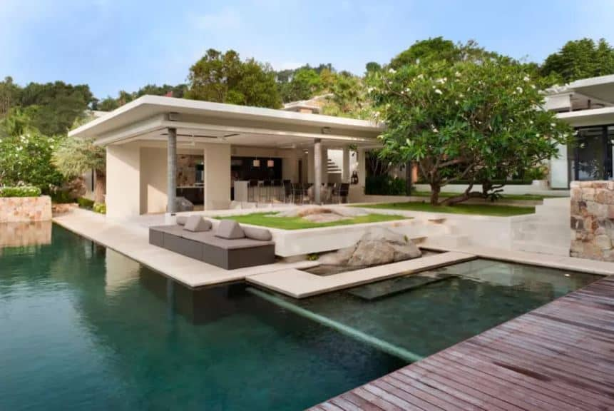 This luxurious home has an outdoor bar and dining area under one large concrete structure by the pool that has  concrete walkways as well as wooden ones surrounding it. This has a beautiful background of decorative rocks, gray outdoor sofas and a large tree with white flowers.