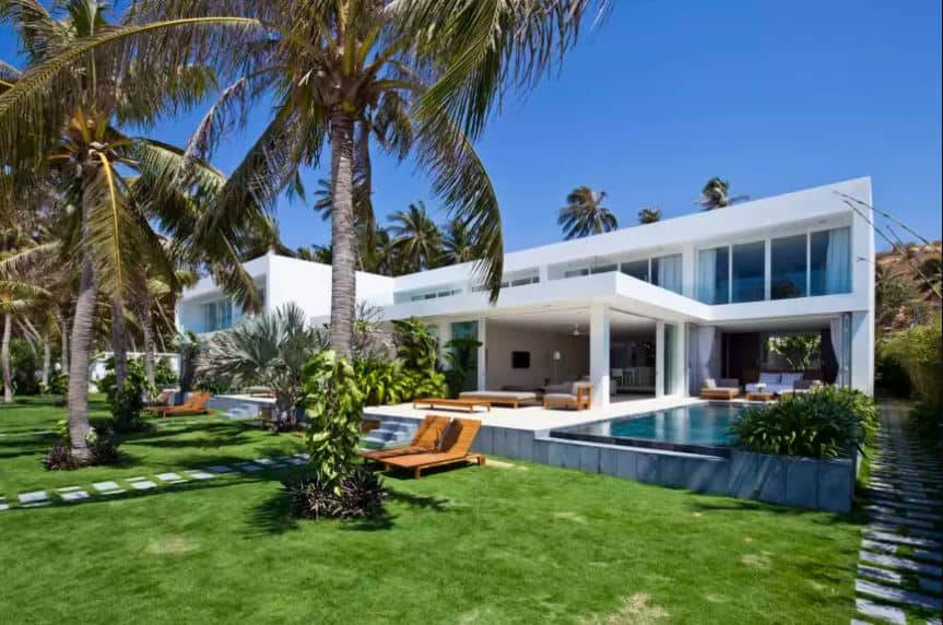 The modern elements of this home works well with the Tropical-style landscaping that gives a counterbalance to its sharp angles and stark brightness. The front yard of this home is filled with a healthy carpet of grass with embedded stone steps for the walkway shaded by tall palm trees.