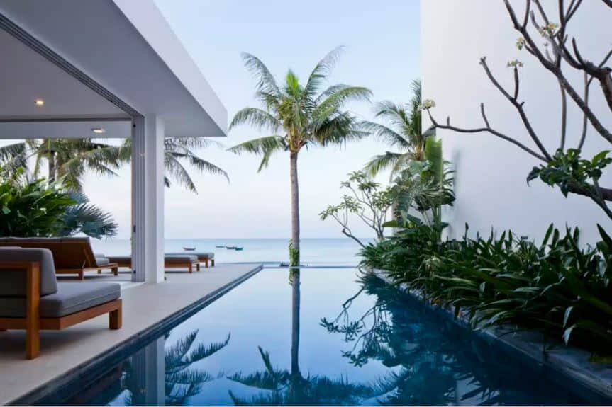 This is the side of the home that faces the ocean. This empty side is fitted with an infinity pool that somehow looks like it merges with the far off ocean. This is further accented with a line of tropical plants on the side that stands out against the white wall.
