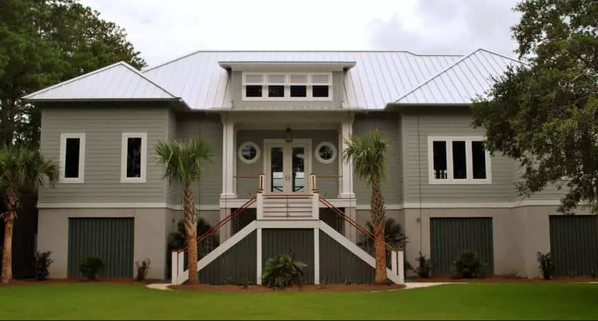 This is the front view of this home that is given a simple Tropical-style landscape. The warm gray exterior walls are lined with shrubs planted on red soil with intervals. The stairs leading up to the main entry is complemented with a couple of palm trees.