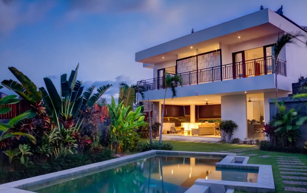 This modern home has a beautiful patio that leads to a lawn of grass with embedded stone steps to form a walkway towards the pool. This pool is adorned with a charming Tropical-style landscaping of colorful tropical plants and shrubs filling the space on one side.