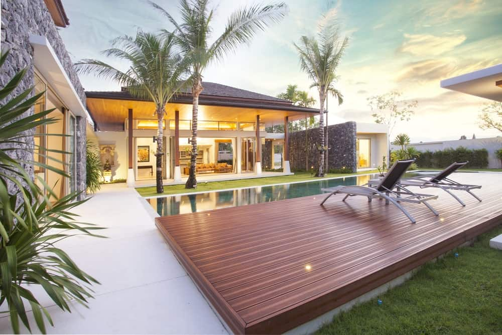 This relaxing Tropical-style landscape has a rectangular pool that is flanked one side by a wooden platform with lawn chairs on it. The other side of this pool has a small carpet of grass with three tall tropical trees that adorns the lovely home.