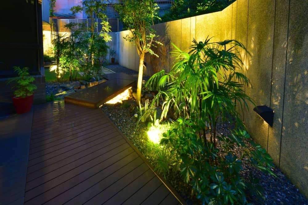 This is the view of the side of the house that has a beautiful wooden walkway adorned with a distinct Tropical-style landscape that has various tropical plants that is lit with warm yellow lights to emphasize the shadows and silhouettes of the leaves on the surrounding concrete fence.